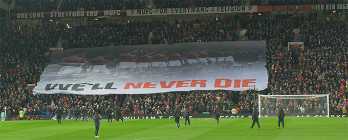 """We'll never die"" banner held up by fans at Stretford End"